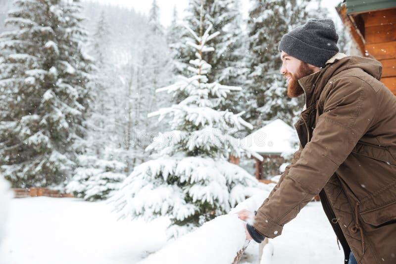 Hombre feliz con la barba que se coloca en bosque del invierno de la montaña imagen de archivo libre de regalías
