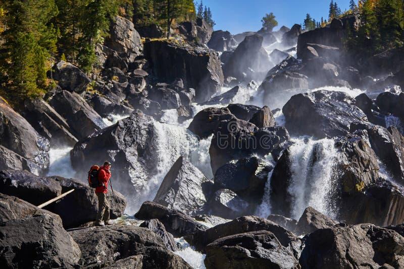 Hombre feliz con la mochila que goza sorprendiendo vacaciones de la forma de vida del viaje de la cascada y del concepto del éxit fotografía de archivo