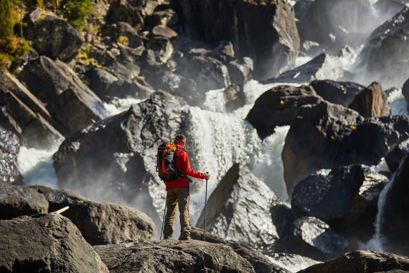 Hombre feliz con la mochila que goza sorprendiendo vacaciones de la forma de vida del viaje de la cascada y del concepto del éxit fotos de archivo