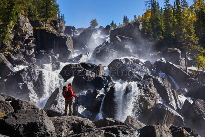 Hombre feliz con la mochila que goza sorprendiendo vacaciones de la forma de vida del viaje de la cascada y del concepto del éxit foto de archivo libre de regalías