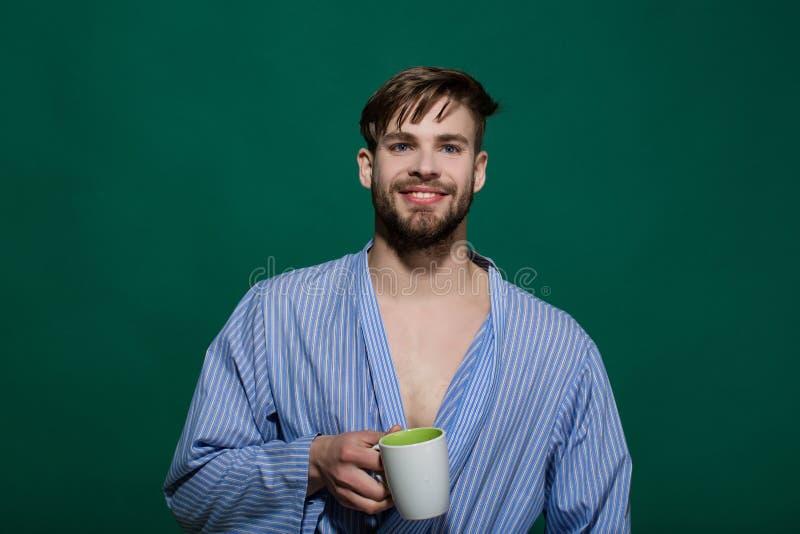 Hombre feliz con la taza en fondo verde foto de archivo