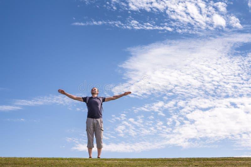 Hombre feliz con los brazos abiertos que se colocan en campo verde fotos de archivo