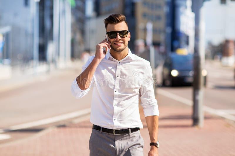 Hombre feliz con smartphone que invita a la calle de la ciudad fotografía de archivo