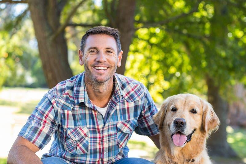 Hombre feliz con su perro casero en parque fotos de archivo