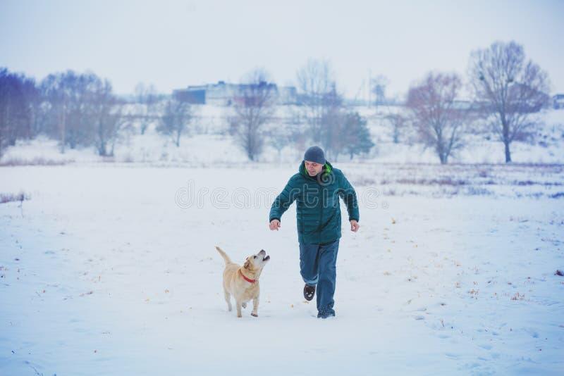 Hombre feliz con un perro que corre a través de un campo nevoso fotografía de archivo