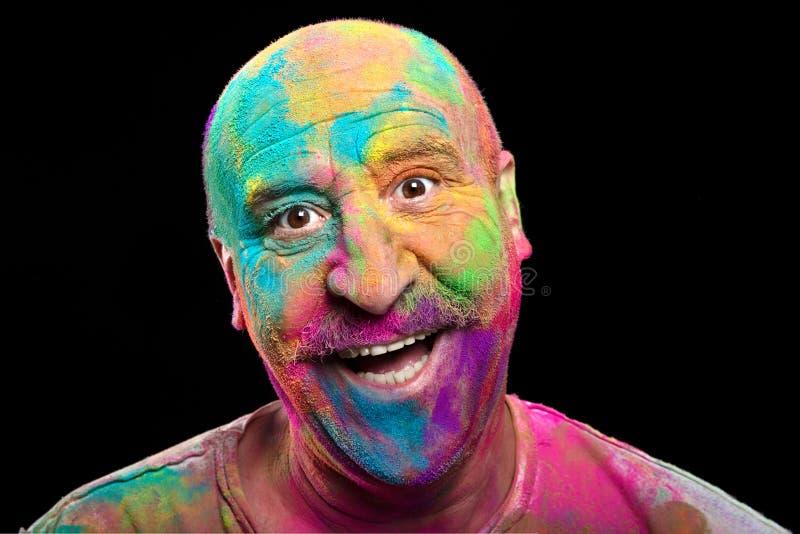 Hombre feliz cubierto en el polvo brillantemente coloreado de Holi fotos de archivo libres de regalías