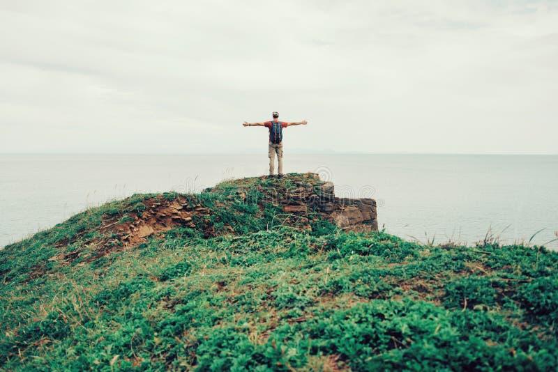 Hombre feliz del caminante que disfruta de la vista del mar foto de archivo libre de regalías