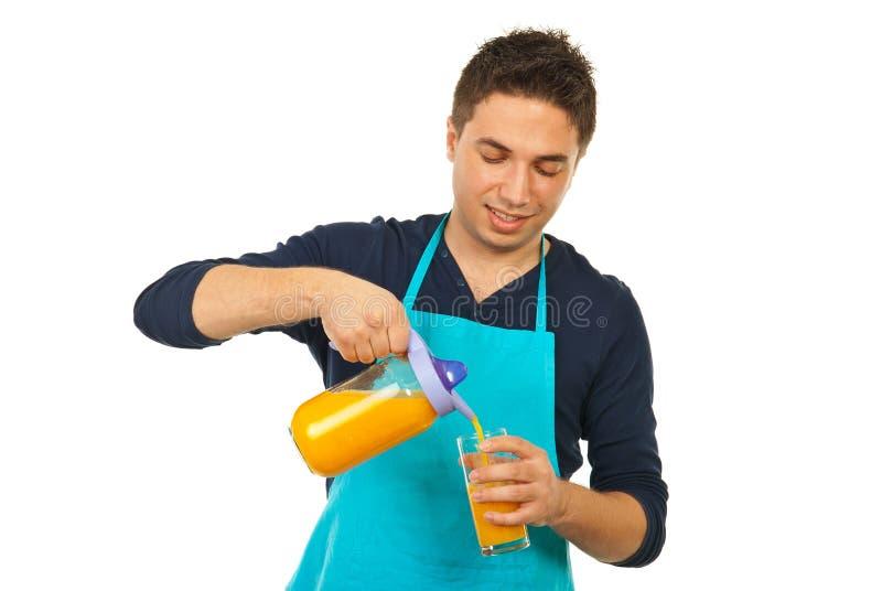 Hombre feliz del cocinero que vierte el zumo de naranja fotos de archivo