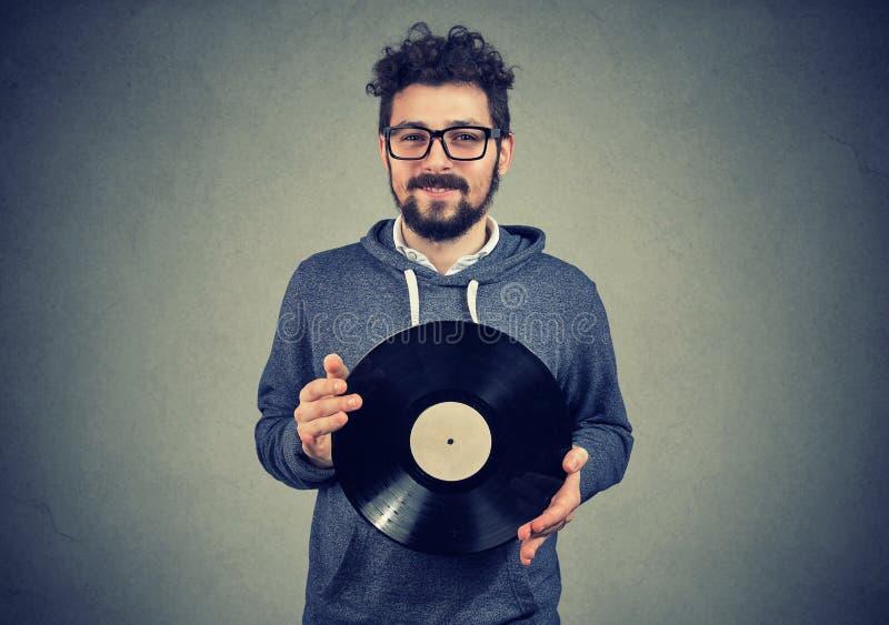 Hombre feliz del inconformista con el disco del vinilo imágenes de archivo libres de regalías