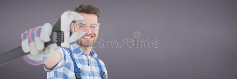 Hombre feliz del mecánico que sostiene una llave contra fondo púrpura fotografía de archivo
