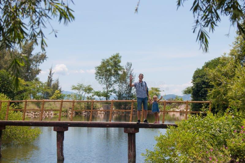 Hombre feliz del padre con su pequeña hija que camina a través del puente de madera del mar imagen de archivo