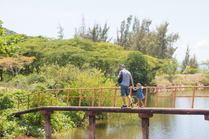 Hombre feliz del padre con su pequeña hija que camina a través del puente de madera del mar fotografía de archivo