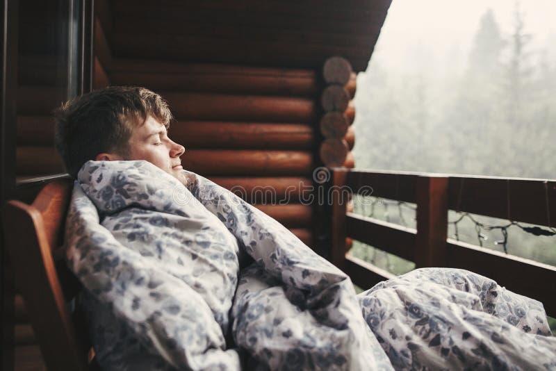 Hombre feliz del viajero que descansa en manta en el pórtico de madera con la opinión sobre el bosque y las montañas Espacio para foto de archivo libre de regalías
