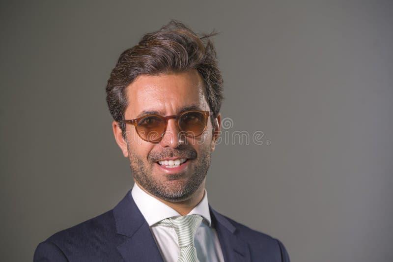 Hombre feliz elegante y hermoso en el traje que presenta para el retrato del negocio corporativo de la compañía relajado y la son foto de archivo