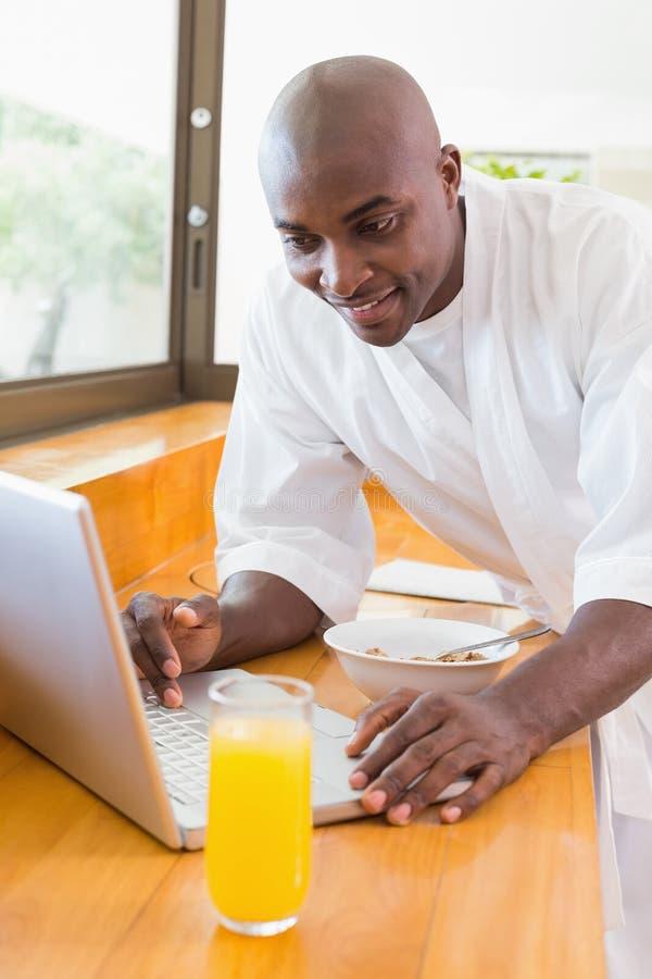Hombre feliz en albornoz usando el ordenador portátil en la tabla foto de archivo libre de regalías