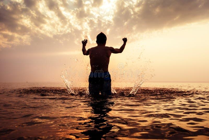 Hombre feliz en el agua imagenes de archivo