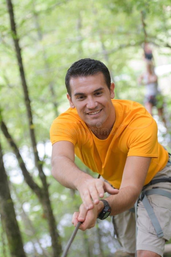 Hombre feliz en el parque extremo de la cuerda con mosquetones foto de archivo