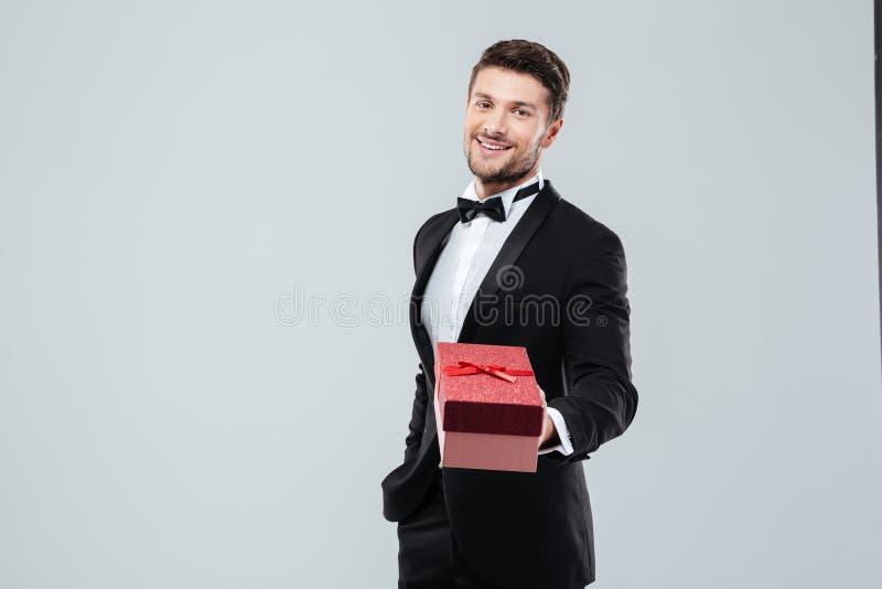 Hombre feliz en el smoking y la corbata de lazo que dan la actual caja foto de archivo