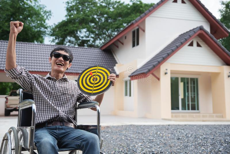 Hombre feliz en la persona asiática de la silla de ruedas que apunta con la sensación feliz del tablero de dardo fotografía de archivo