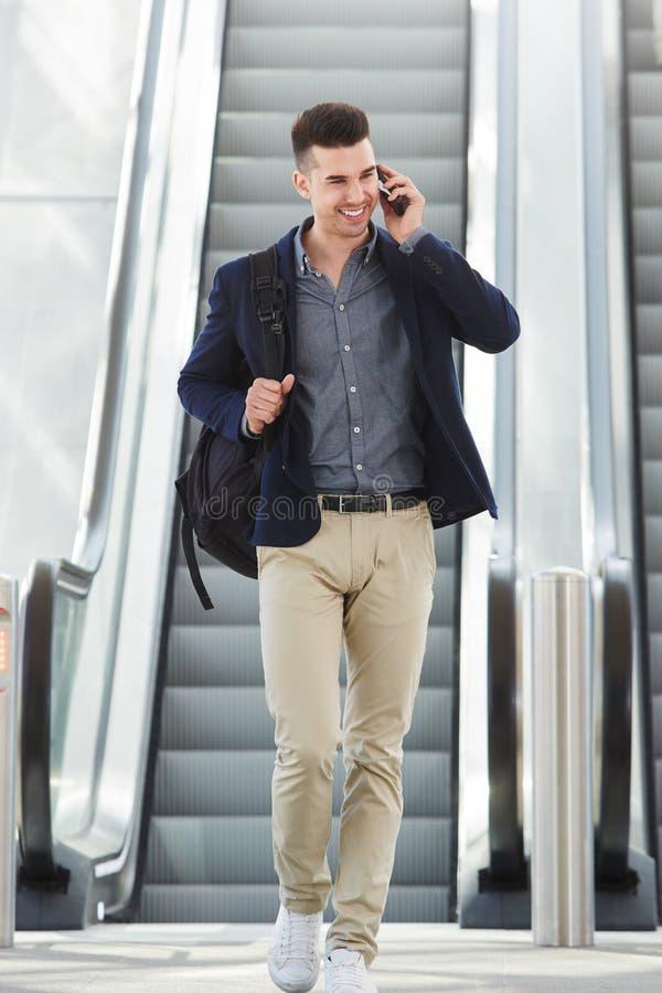 Hombre feliz en llamada telefónica por la escalera móvil imagen de archivo libre de regalías