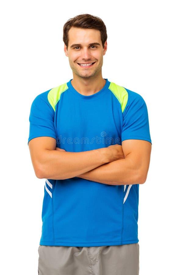Hombre feliz en los brazos derechos de la ropa de deportes cruzados imágenes de archivo libres de regalías