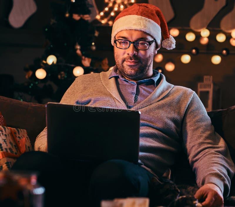 Hombre feliz en los vidrios que frotan ligeramente un gato y que usan el ordenador portátil mientras que se sienta en el sofá en  fotos de archivo