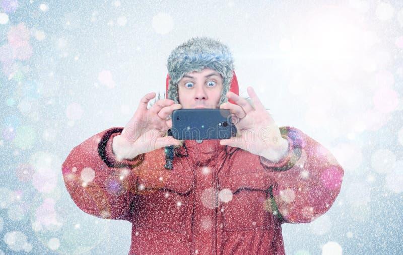 Hombre feliz en ropa del invierno con smartphone Frost, sol, nieve, señala por medio de luces imagen de archivo