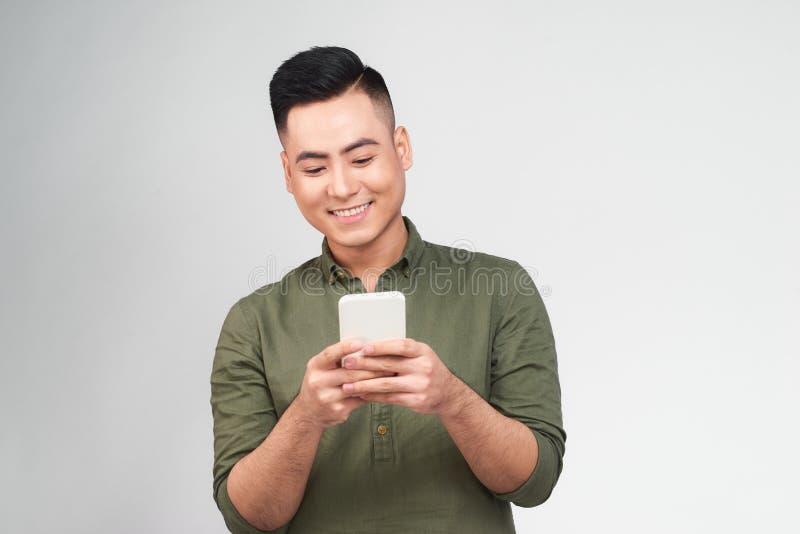 Hombre feliz en vidrios que mecanografía SMS en fondo gris imagenes de archivo