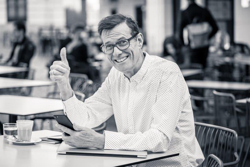 Hombre feliz hermoso en su 60s que comprueba mensajes en su pulgar de la demostración del teléfono móvil para arriba en viejo hom fotos de archivo