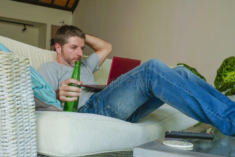 Hombre feliz hermoso joven que sienta en casa el sofá del sofá que trabaja en línea con el ordenador portátil usando la consumici foto de archivo libre de regalías