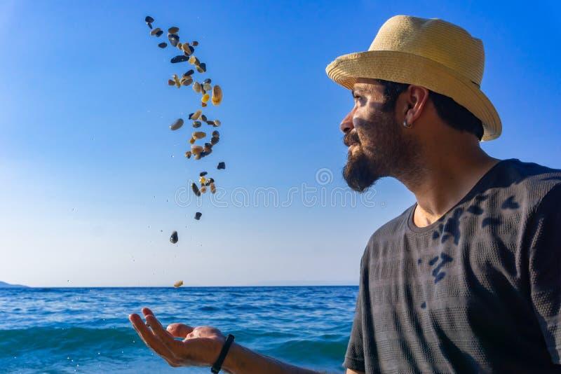 Hombre feliz hermoso que se divierte con los guijarros en la playa de la puesta del sol El hombre lanza piedras de la playa en el fotos de archivo libres de regalías