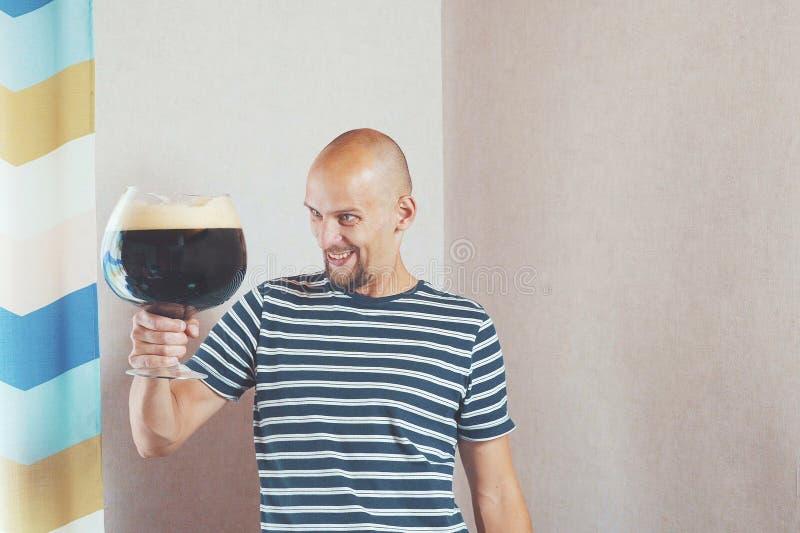 Hombre feliz, joven con una taza muy grande de cerveza Él ríe y disfruta, y entonces las bebidas imagen de archivo