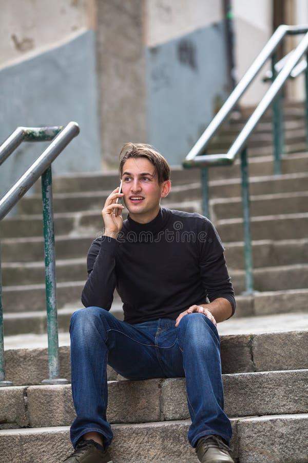 Hombre feliz joven que habla en el teléfono al aire libre fotos de archivo libres de regalías