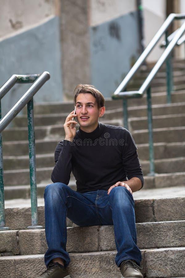 Hombre feliz joven que habla en móvil mientras que se sienta en pasos de piedra al aire libre fotografía de archivo libre de regalías