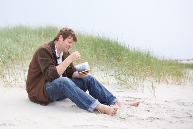 Hombre feliz joven que se relaja en las dunas de arena de la playa de San Pedro imágenes de archivo libres de regalías