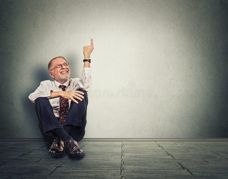 Hombre feliz mayor que se sienta en piso con las piernas cruzadas y que destaca imagenes de archivo