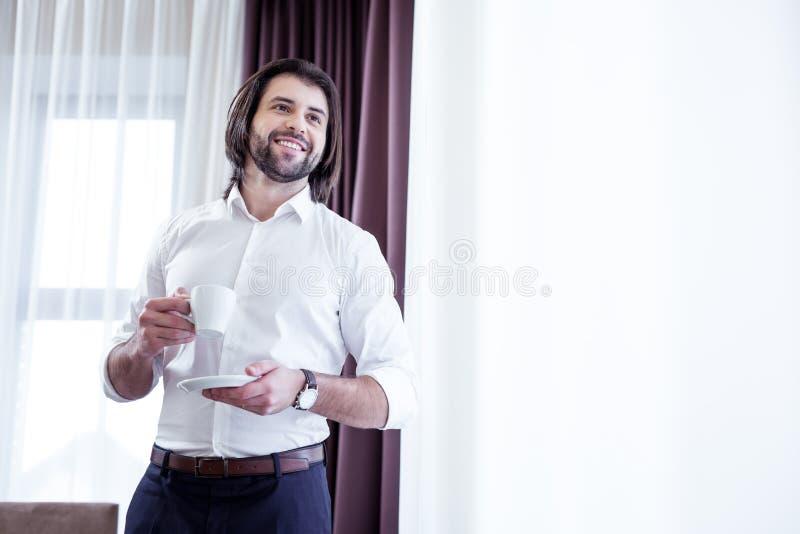 Hombre feliz positivo que goza de su café delicioso imágenes de archivo libres de regalías