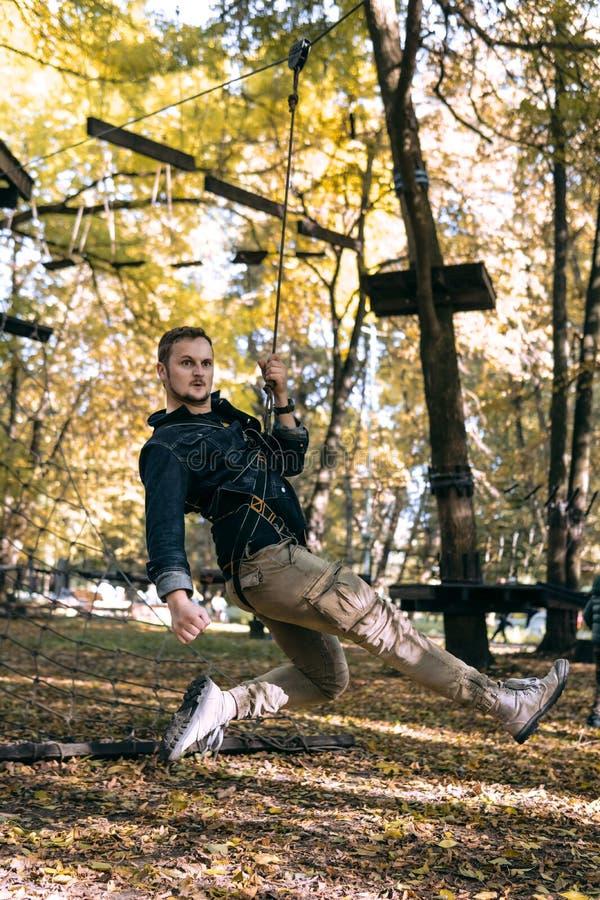 Hombre feliz que cuelga en una cuerda de la seguridad, engranaje que sube en obstáculos de la aventura de un paso del parque en e imagen de archivo libre de regalías