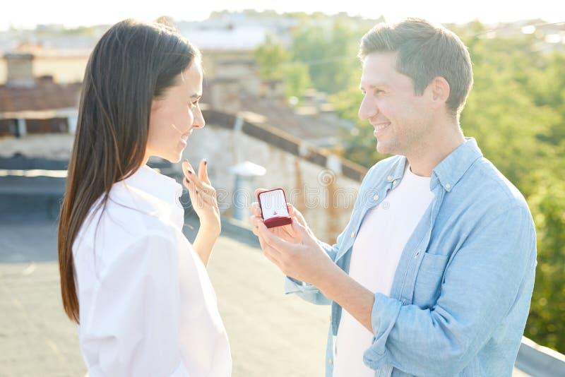 Hombre feliz que da el anillo de compromiso a la mujer querida foto de archivo libre de regalías