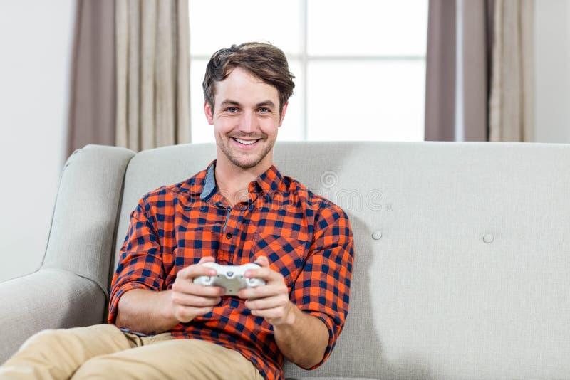 Hombre feliz que juega a los videojuegos imagenes de archivo