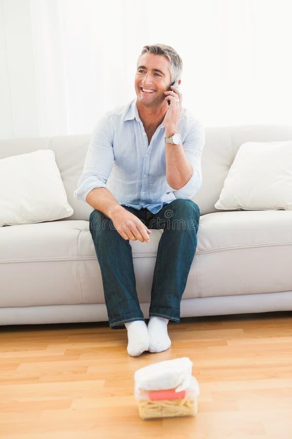 Hombre feliz que llama por teléfono en el sofá imagenes de archivo
