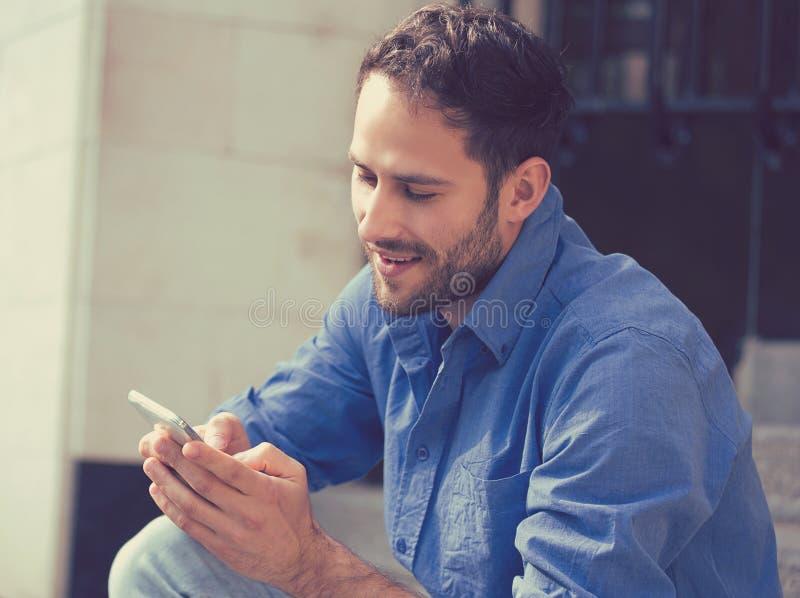 Hombre feliz que manda un SMS en el teléfono que se sienta en las escaleras fuera de la oficina imagenes de archivo