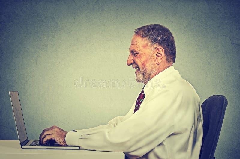 Hombre feliz que mecanografía en su ordenador portátil imágenes de archivo libres de regalías