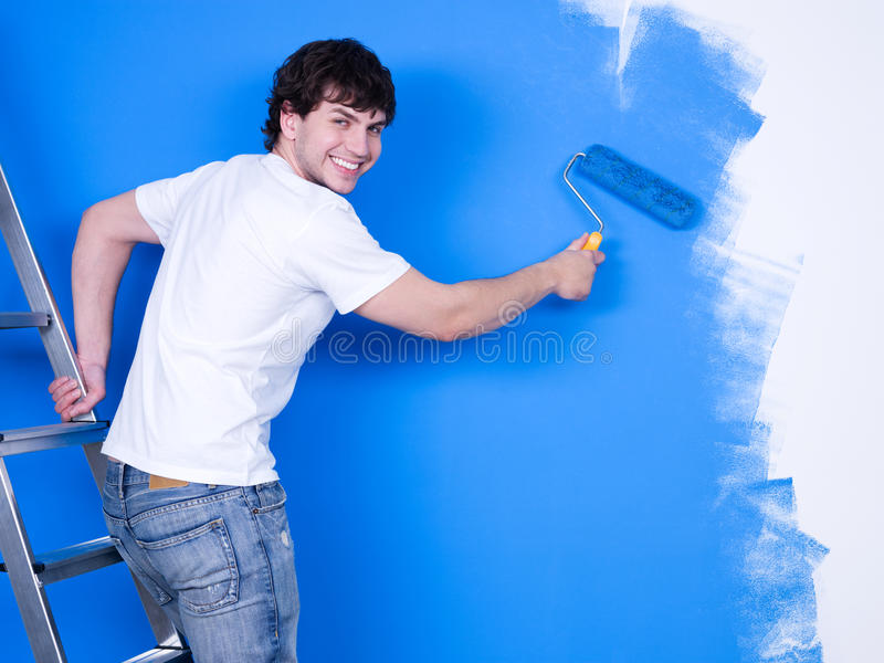 Hombre feliz que pinta la pared imagen de archivo