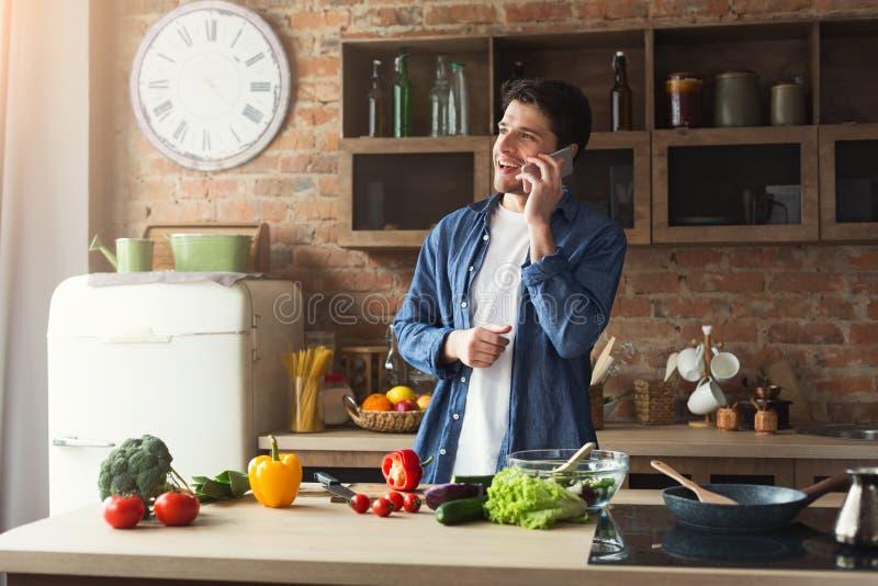 Hombre feliz que prepara la comida sana en la cocina casera foto de archivo libre de regalías