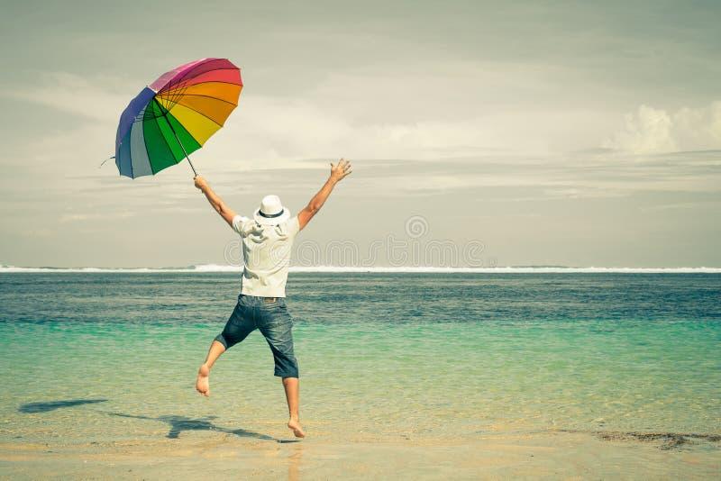 Hombre feliz que salta sobre el mar Playa de la arena imagenes de archivo
