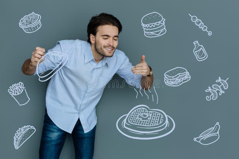 Hombre feliz que se cierra los ojos y que huele una comida lista foto de archivo libre de regalías