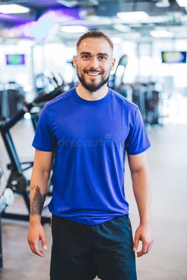 Hombre feliz que se coloca en un gimnasio imagen de archivo