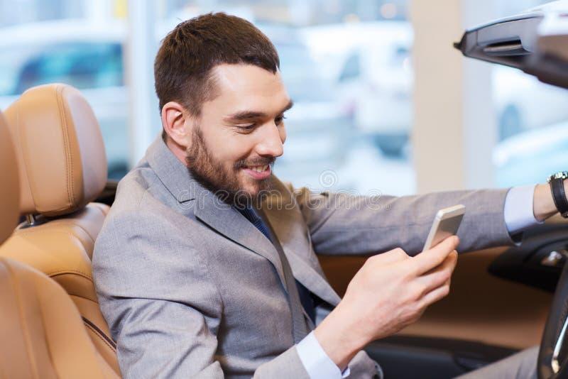 Hombre feliz que se sienta en coche en el salón del automóvil o el salón fotografía de archivo libre de regalías