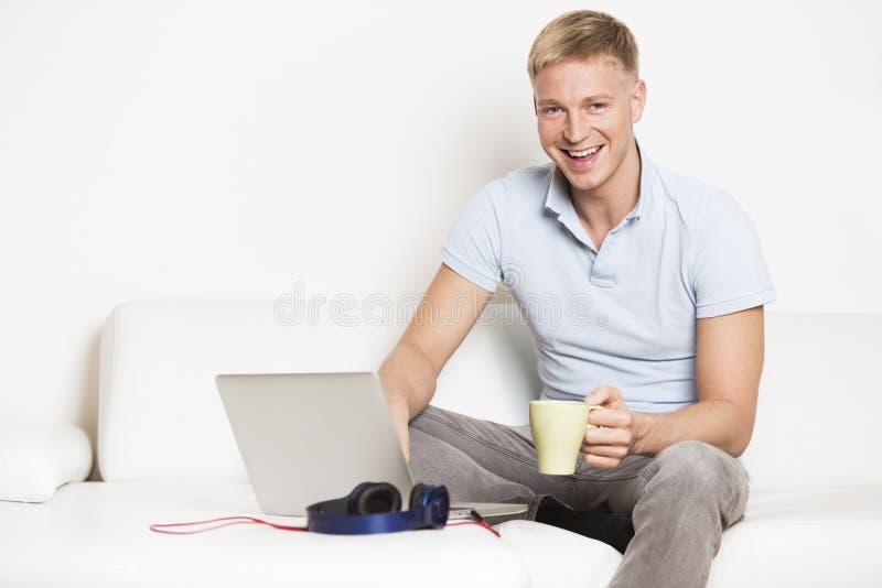 Hombre feliz que se sienta en el sofá con el ordenador portátil y el café de consumición. imagen de archivo